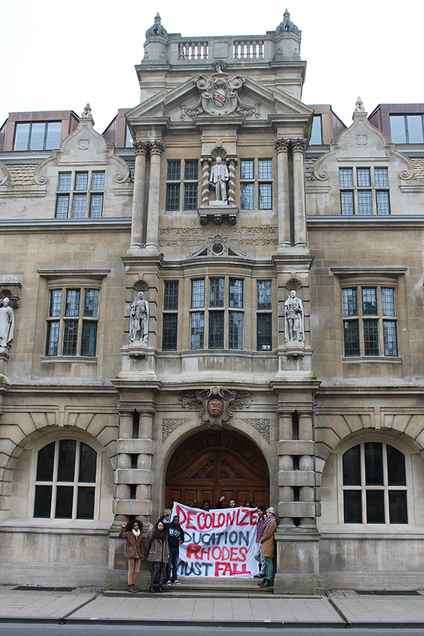 Protesters outside Oriel College with Rhodes above them.